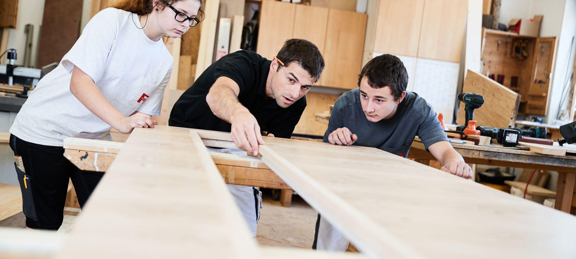 Tischlermeister mit seinen Tischlereilehrlingen